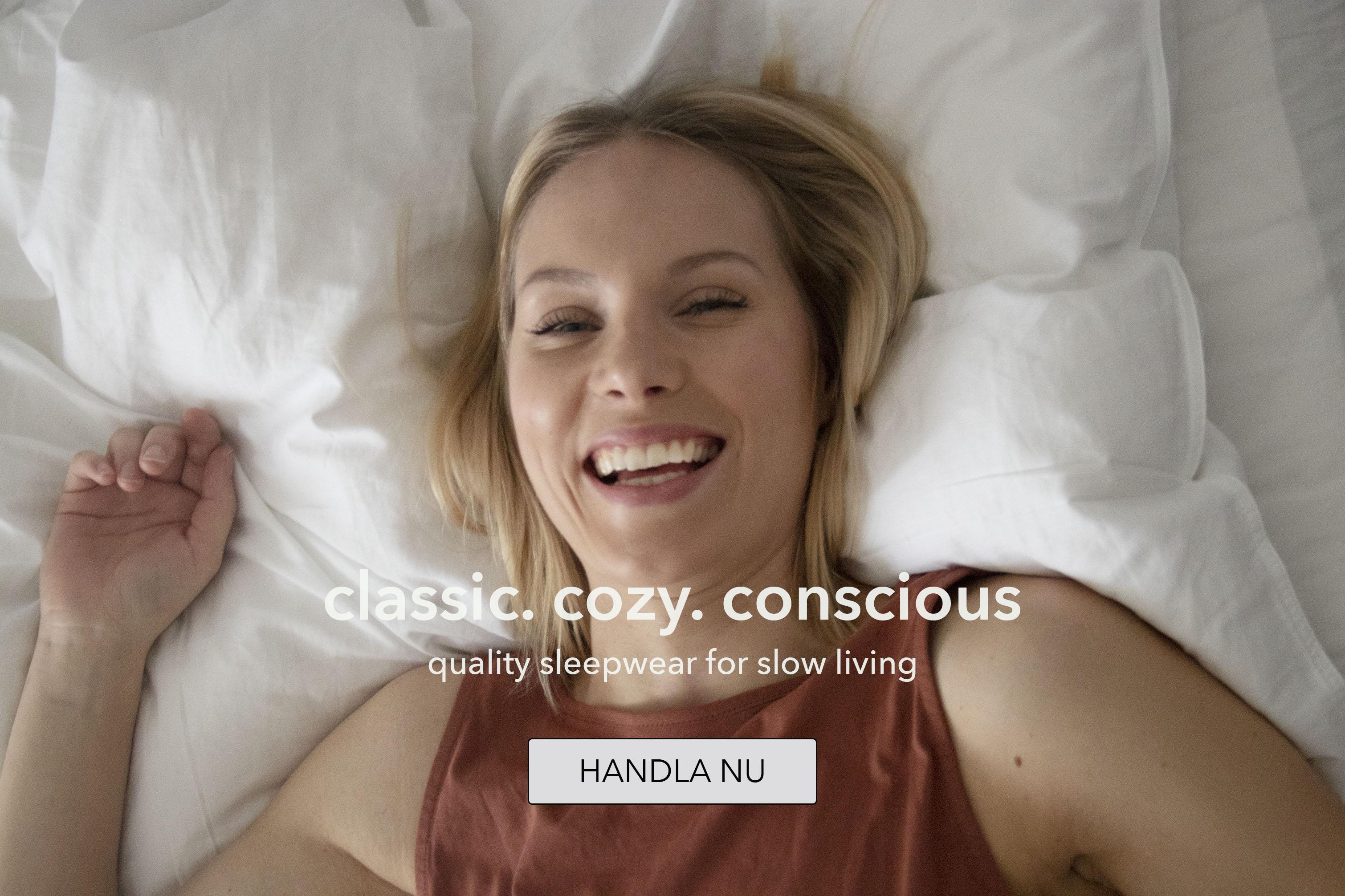 Kvinna ligger i sängen och ler i nattlinne från The Sleepy Collection
